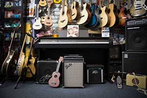 Photograph of acoustic guitars, amplifiers and a keyboard piano